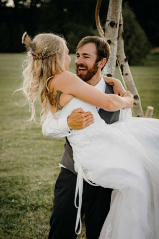 groom carrying bride with both laughing