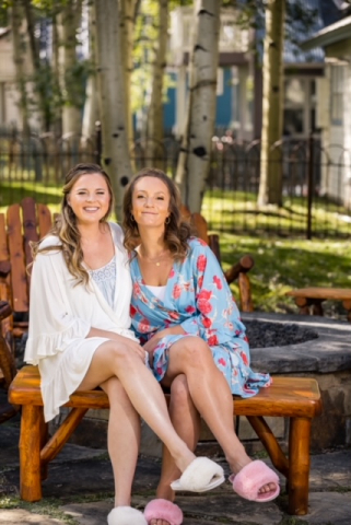 bride and bridesmaid sitting on a bench in bathrobes smiling
